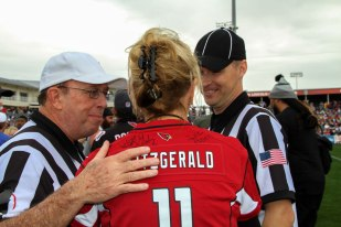 Mayor Wolcott discussing the game with refs at the 14th Annual Celebrity Flag Football Challenge